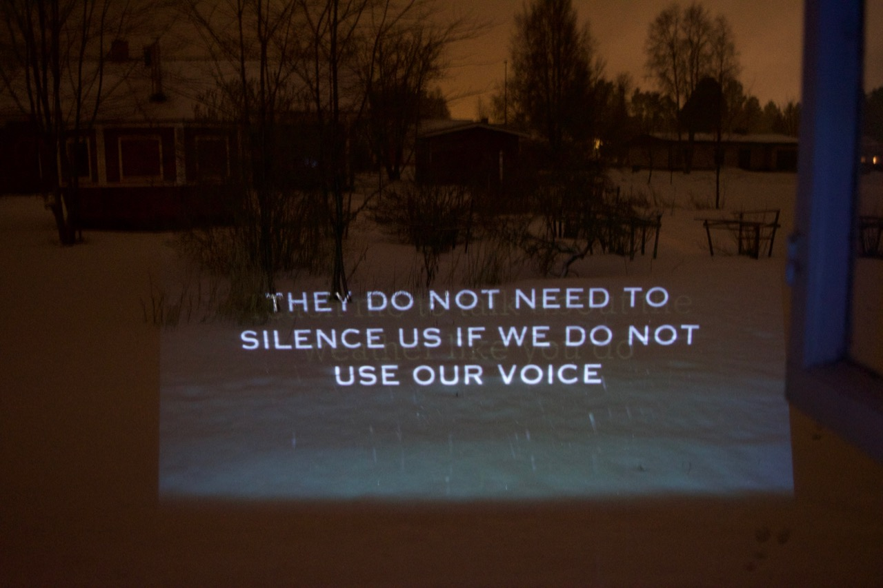 A projection showing a snowy landscape with the silhouettes of the bare branches of trees in winter. Overlaid is the text 'THEY DO NOT NEED TO SILENCE US IF WE DO NOT USE OUR VOICE.'
