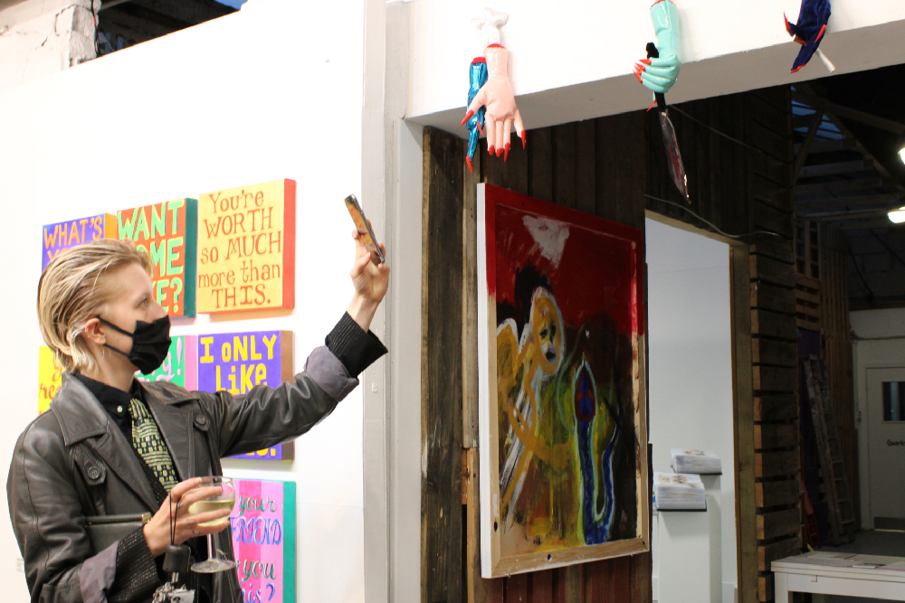 a person with slicked back blonde hair, wearing a leather jacket, cravat and black facemask, carries a glass of white wine and takes a photograph of an artwork on their phone. Behind them is a grid of brightly coloured square canvasses and in front of them are a series of brightly coloured sculptures of hands.