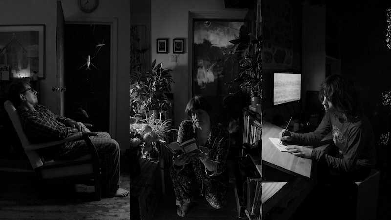 A screen is split into three. The image is black and white. On the left a middle aged man in pyjamas sits relaxed in a semi reclined pose in an arm chair. His arms are crossed in his lap and he has barefeet. Behind him a screen in a doorway has images of pondskaters on it. The centre image shows a middle aged white woman wearing pyjamas kneeling down between a table and a bookcase. There are flowers on the table. She is reading a book. On a screen behind her clouds can be seen. The right image shows a young white boy sat drawing on paper next to a screen showing static pattern. Behind him is a projected image of foam on water.