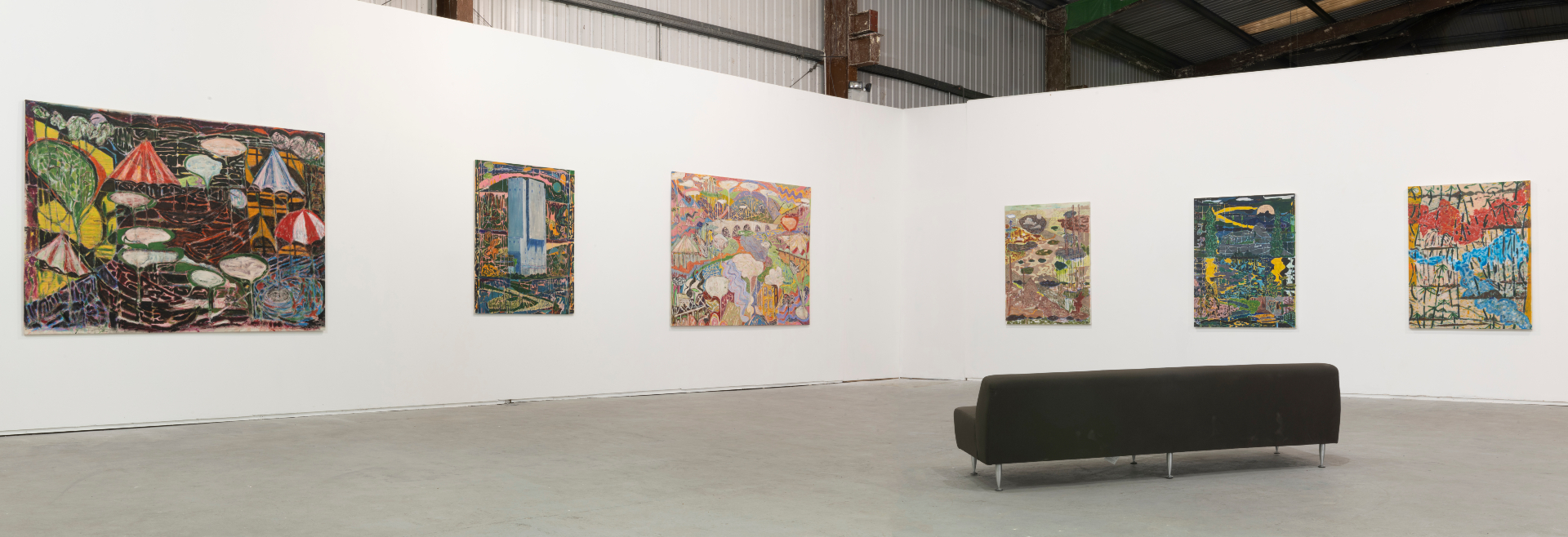 photograph of white-walled gallery space with a black sofa face six paintings