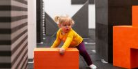 small child grasps large red block in art exhibition