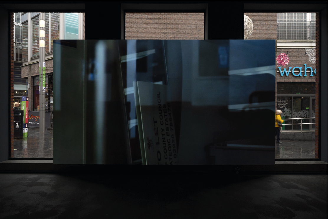 Exhibition image of artist film displayed at Bluecoat, with pedestrians visible through the window in the background