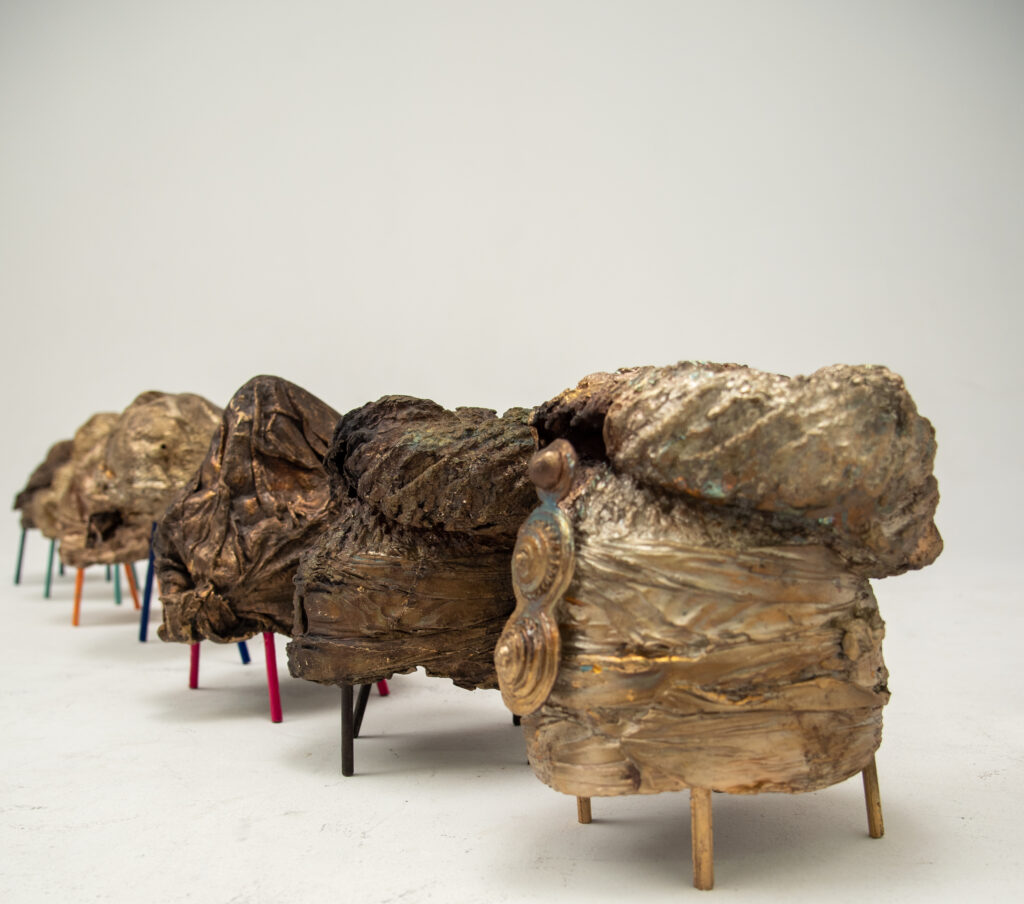 A series of bronze sculptures of elaborate Afro hairstyles for women mounted on short and colourful wooden sticks.