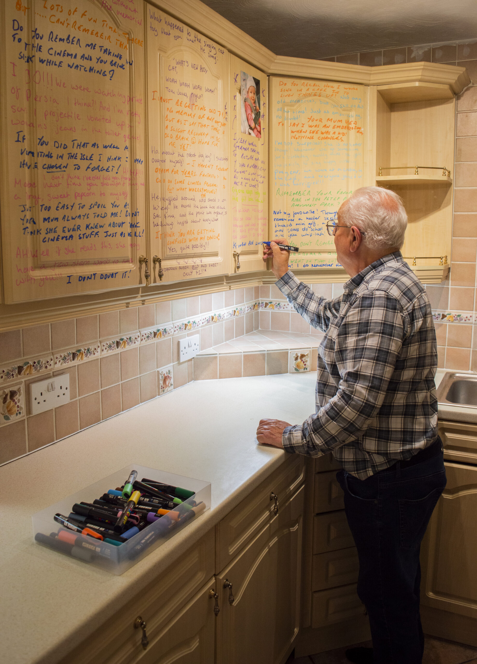 An older white man with white hair, glasses and wearing a checked shirt is facing away from the camera and writing on kitchen cabinet doors using paint markers. There is multi coloured writing all over the cabinets and a box of markers in the foreground.