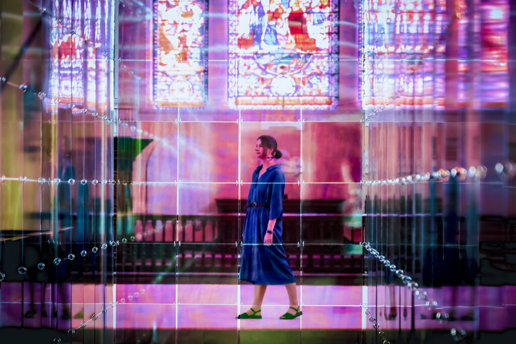 Stained glass windows and a white woman in a blue dress with brown hair tied back are viewed through coloured glass or perspex, the whole image is bathed in pink light.