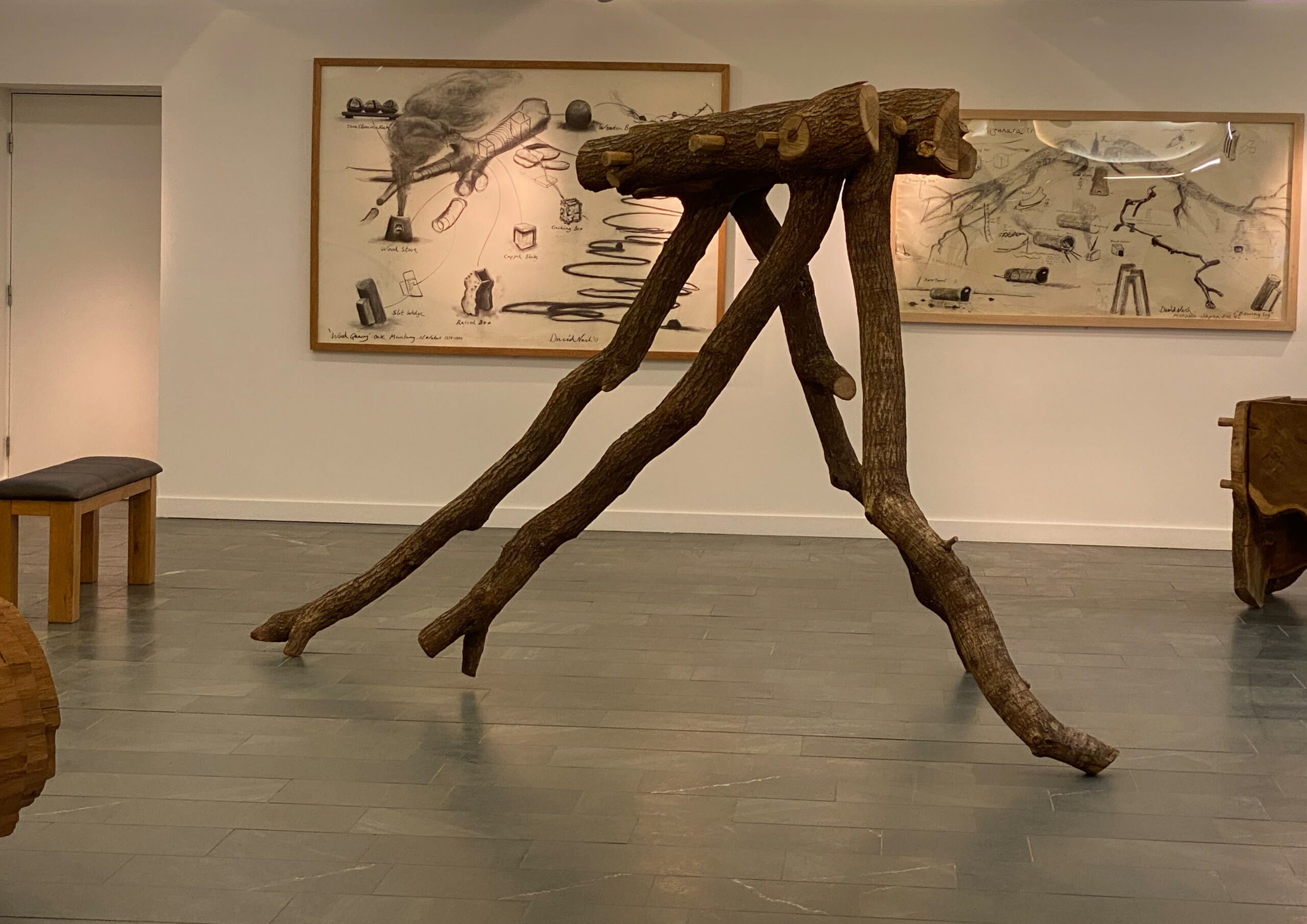 The image shows a wooden sculpture resembling a tree trunk supported by four bowing legs in the centre of the frame, with drawings of tree trunks in frames behind it on the gallery wall.