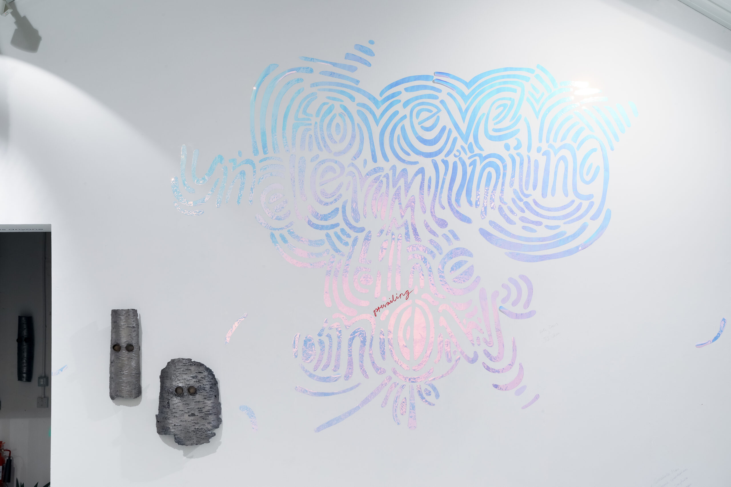 Installation wall painting with words 'Forever Underminging the prevailing Now' in blue and pink. Two metal mask sculptures wall mounted to the left.