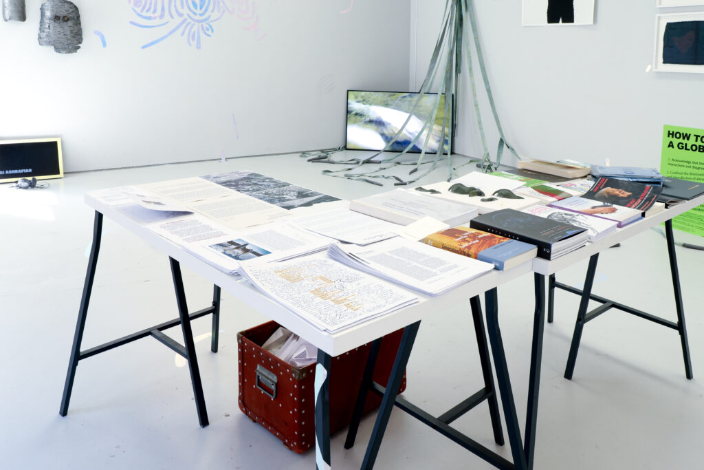 A table in the centre of the room with printed materials and books.