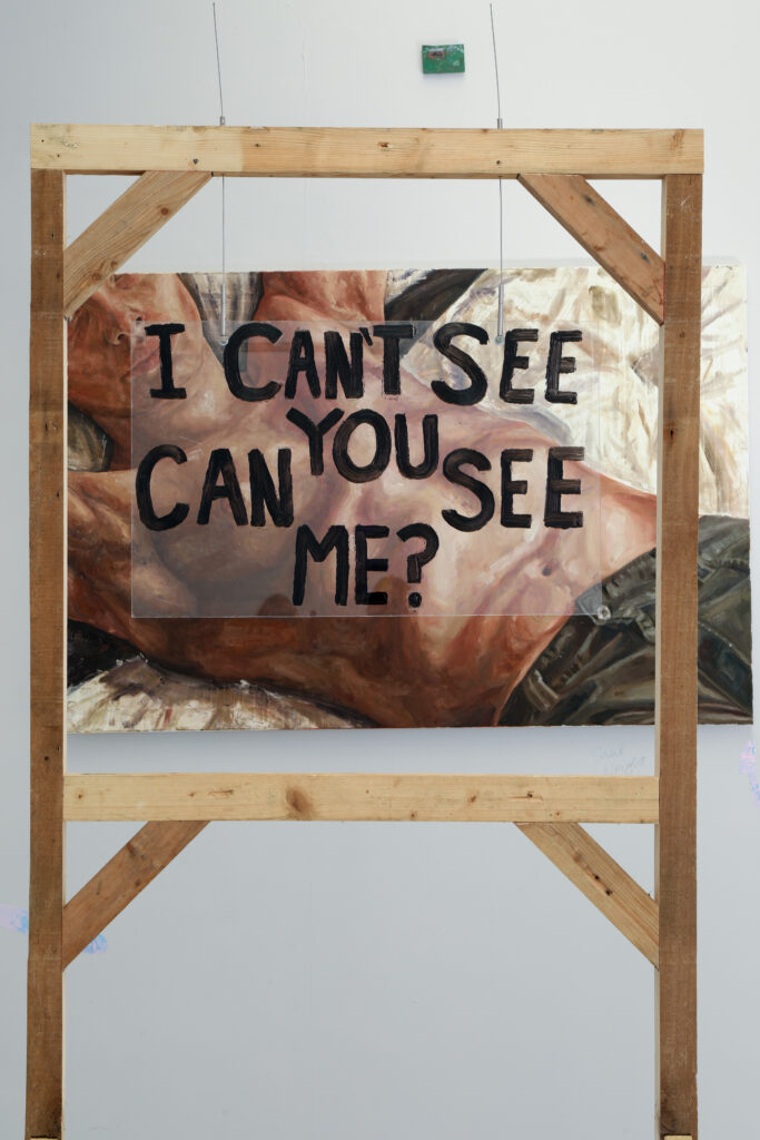 A wooden framework in foreground with words 'I can't see you can you see me?' on perspex sheet; a painting of a reclined man in jeans and bare torso in background.
