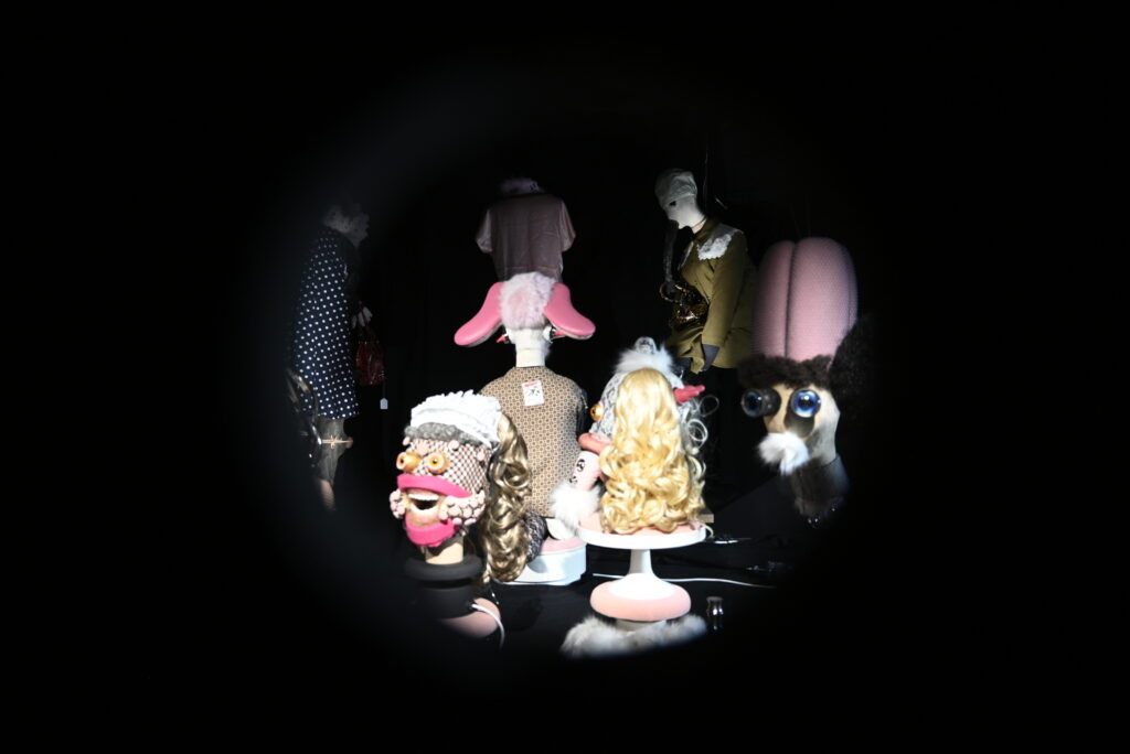 A black background with heads and figures visible in the centre through a peephole. The heads and figures are 'grotesques', constructed from other parts of mannequins and waste materials.