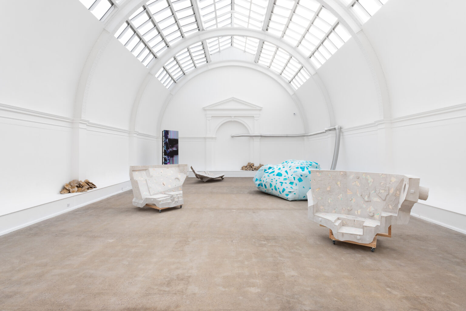 An image showing the full installation from a central perspective, with a grouping of sculptures and a clear view of the glass ceiling.