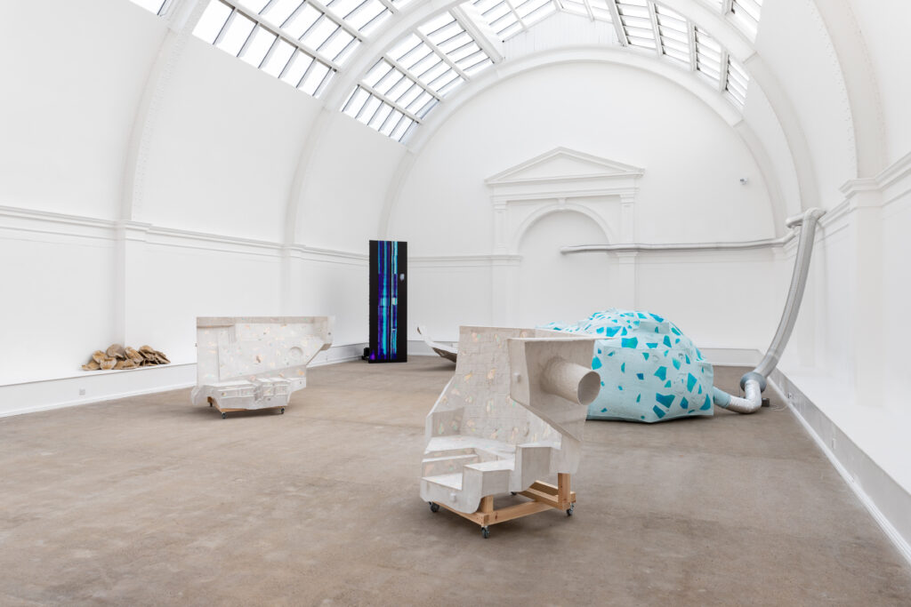 An image showing the full view of the installation from the right of the room, with a grouping of sculptures of different industrial materials.