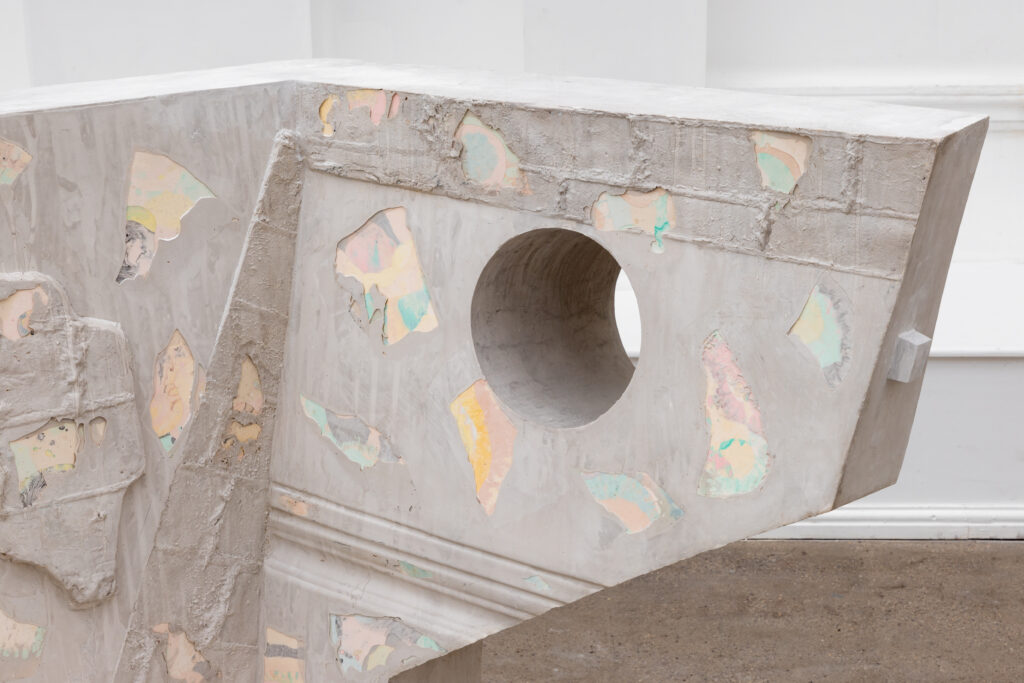 An image showing the detail of one of the sculptures, which appears to be cast. The superficial layer flakes off in places to show a pastel, multi-coloured underlayer