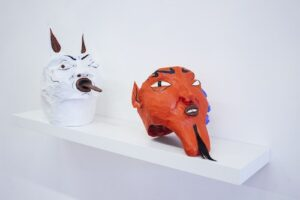 Two papier mache masks sit on a white shelf which is mounted on a white wall. One is white and one is red, and they appear to be demons or folkloric figures.