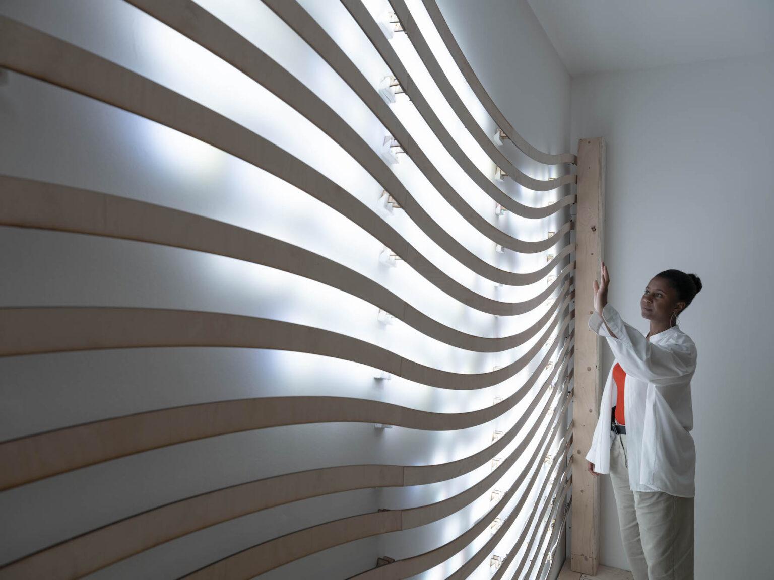 The artist stands beside a wavy sculptural wall installation, backlit.