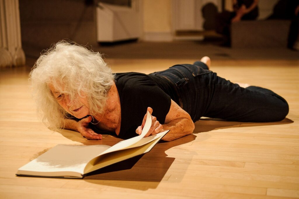 A photo of a woman lying on her front in a studio space, reading from a notebook.